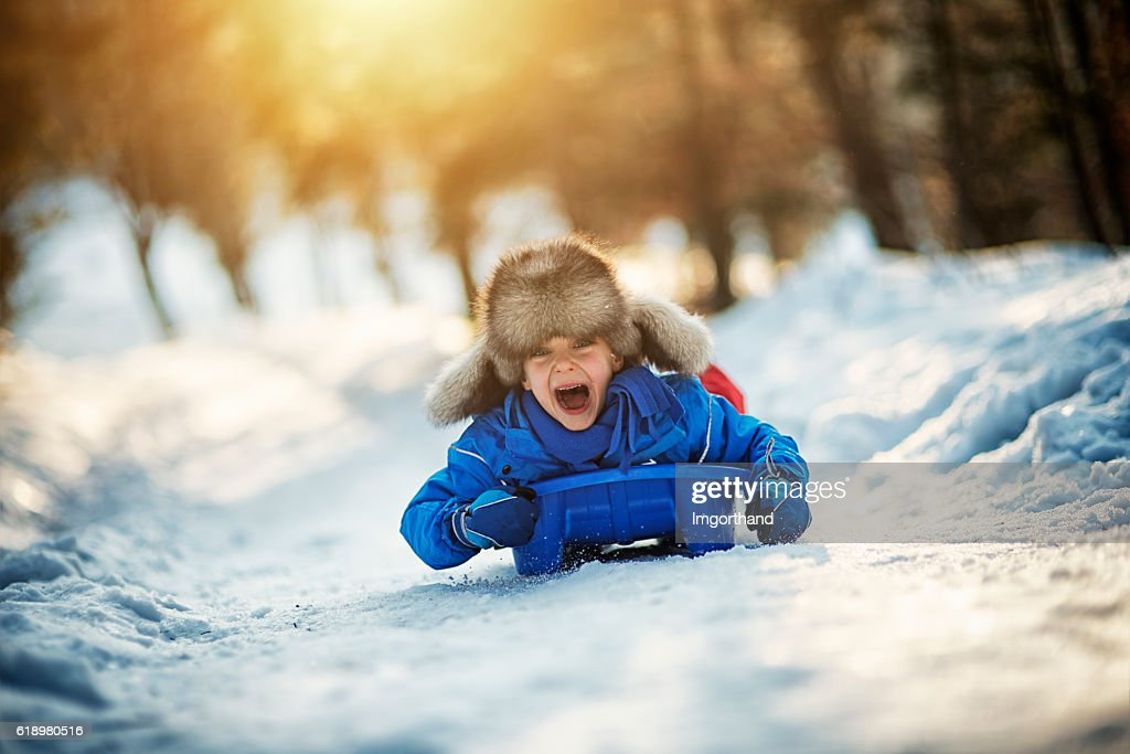 Little boy having extreme fun on his sled : Stock Photo