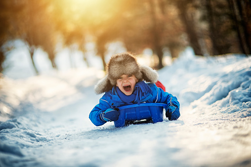 Little boy having extreme fun on his sled 618980516