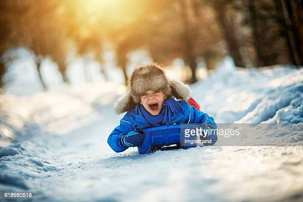 little boy having extreme fun on his sled - winter sport stock pictures, royalty-free photos & images