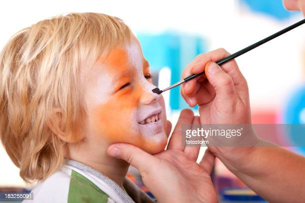 Little boy having face painted on birthday party
