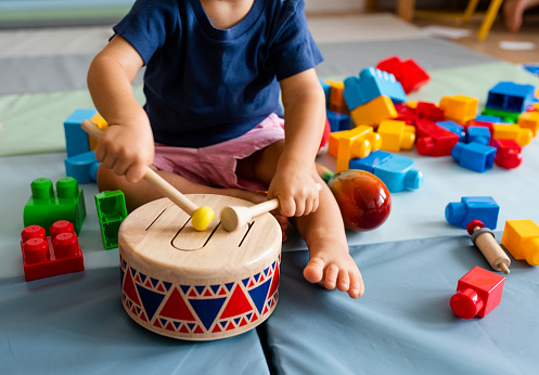 Little boy having fun and playing wooden toy drum 1097258406