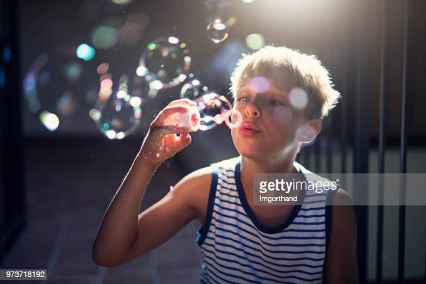 little boy having fun blowing bubbles - bubble stock pictures, royalty-free photos & images