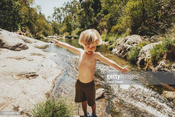 little boy having fun by the river at nature in summer - light natural phenomenon stock pictures, royalty-free photos & images