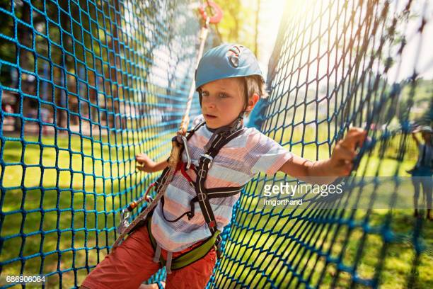 Little boy having fun during ropes course in adventure park