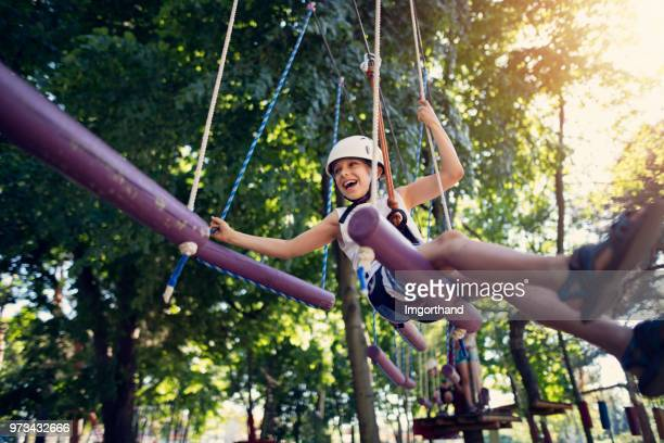 little boy having fun during ropes course in adventure park - outdoor pursuit stock pictures, royalty-free photos & images