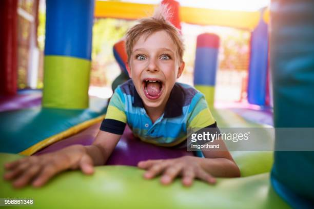 Little boy having fun in inflatable castle playground