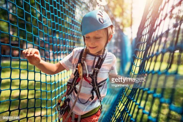 Kleinen Jungen Spaß in Hindernisse Kurs Abenteuerpark