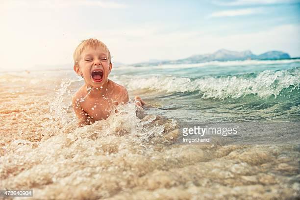 Petit garçon s'amusant dans la mer