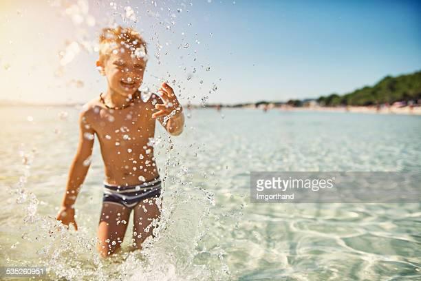Little boy having fun in sea splashing