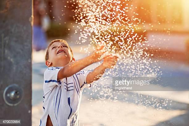 Kleine Junge Spaß im Wasser park fountain