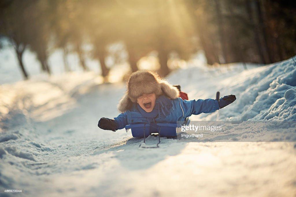 Niño divirtiéndose en su sled en invierno worest. : Foto de stock