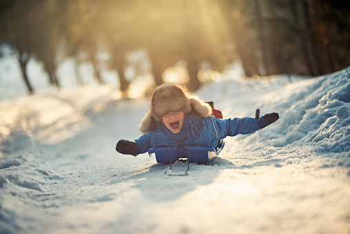 Little boy having fun on his sled in winter worest. 486920044