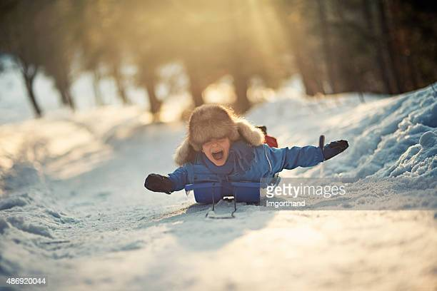 little boy having fun on his sled in winter worest. - winter sport stock pictures, royalty-free photos & images