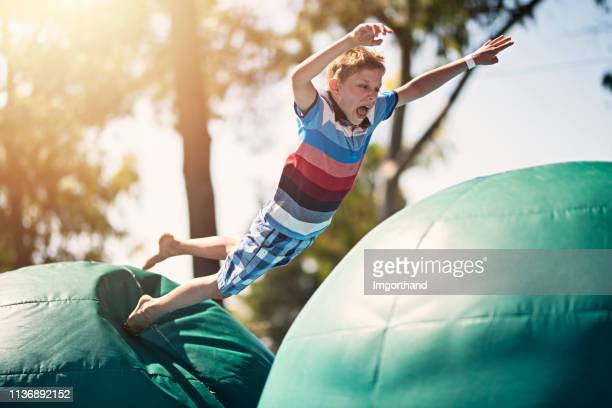 little boy having fun on inflatable obstacle course - obstacle course stock pictures, royalty-free photos & images