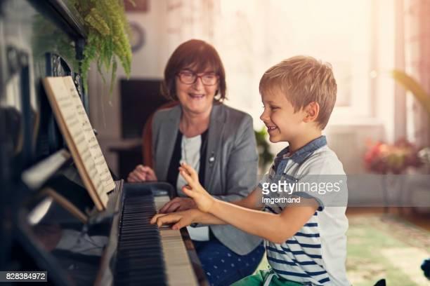 Little boy having fun piano lesson