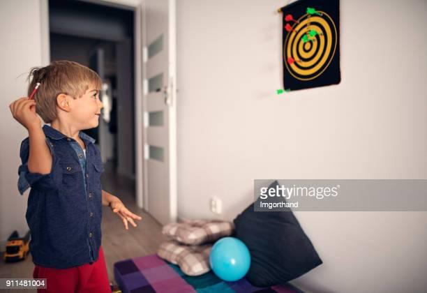 Little boy having fun playing darts