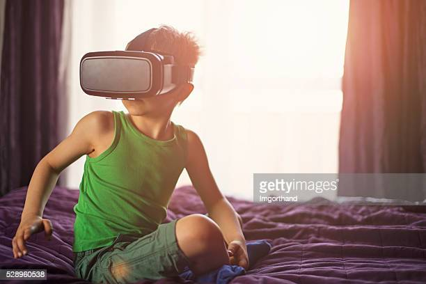 little boy having fun playing with virtual reality headset - imgorthand stock photos and pictures