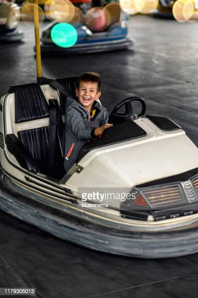 little boy having fun riding bumper car - green car crash stock pictures, royalty-free photos & images