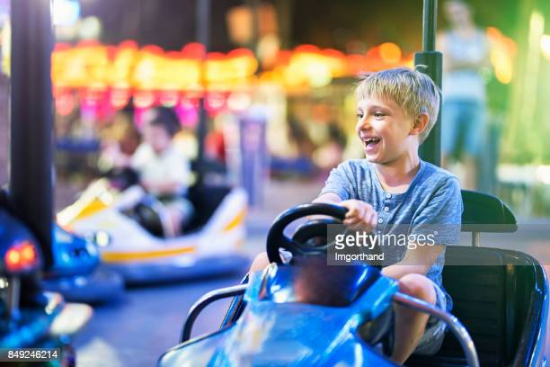 little boy having fun riding bumper car - land vehicle stock pictures, royalty-free photos & images