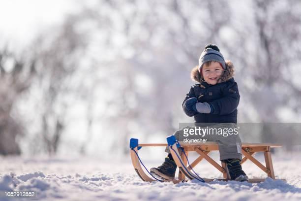 Little boy having fun while sliding on a sledge during winter season.
