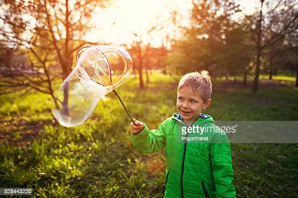 Little boy having fun with big bubbles on spring evening