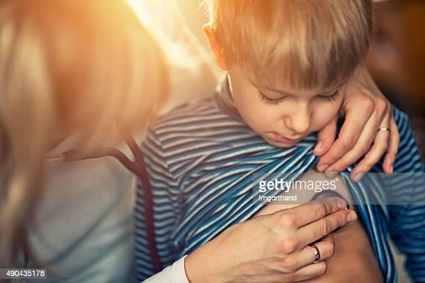 Kleine Jungen, die medizinische Untersuchung aufzulegen wie zu Hause fühlen.