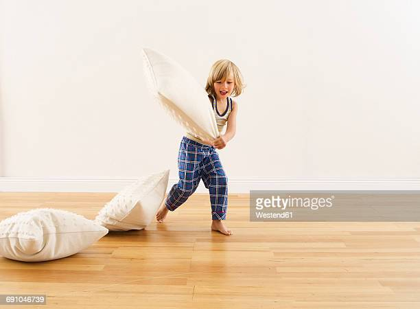 Little boy having pillow fight with himself