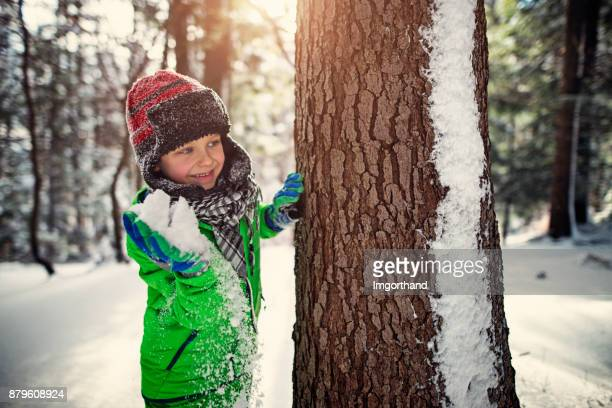 Little boy having showball fight in winter forest