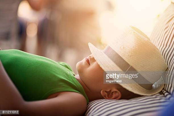 Little boy having siesta in the middle of summer day
