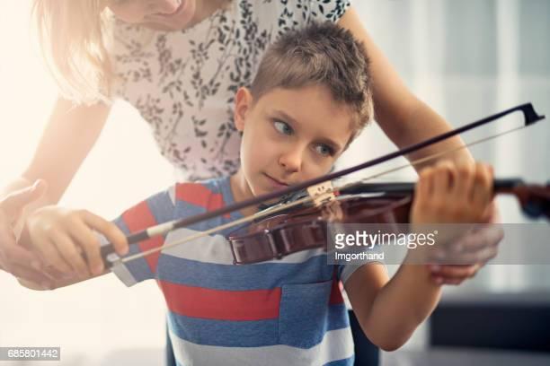 Little boy having violin lesson