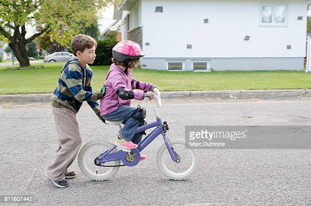little boy helping his sister biking - children only stock pictures, royalty-free photos & images
