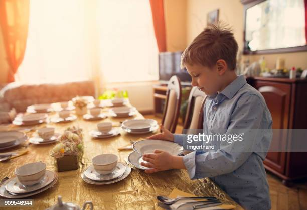 Little boy helping in setting the table for traditional easter breakfast
