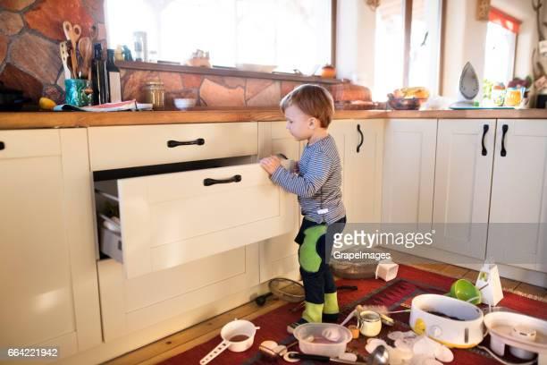 Kleiner Junge hilft mit Haus Hausarbeiten, Organisation von Küchenschublade