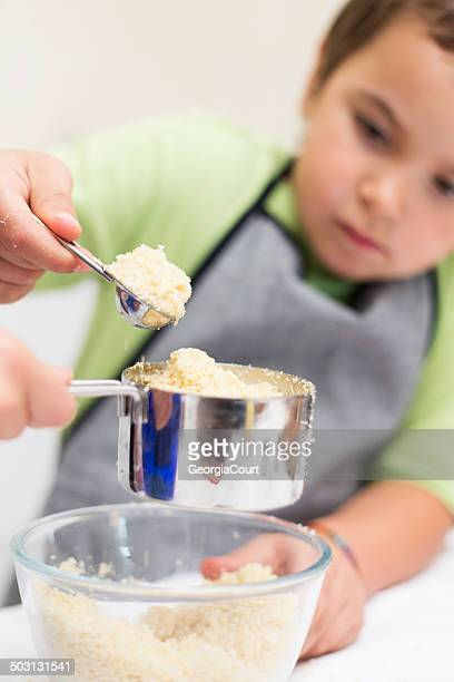 little boy helping with the cooking - measuring cup stock pictures, royalty-free photos & images
