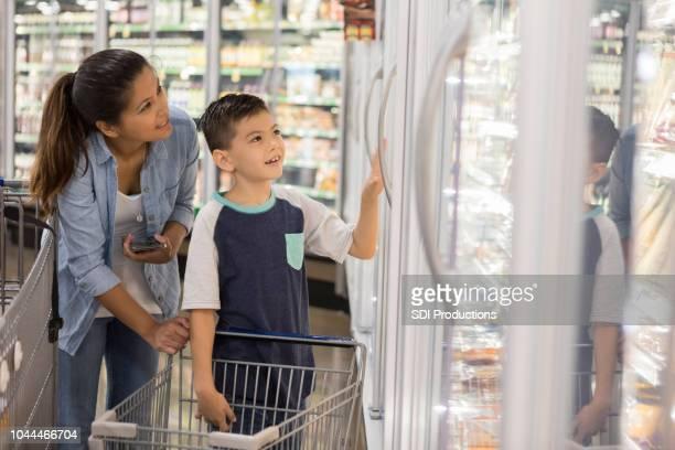 kleine jongen helpt zijn moeder winkel voor boodschappen - zuidoost aziatische etniciteit stockfoto's en -beelden
