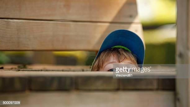 little boy hiding at playground - wachsamkeit stock-fotos und bilder