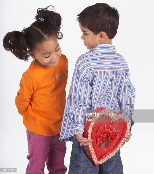little boy hiding box of candy from little girl - naughty valentine stock pictures, royalty-free photos & images