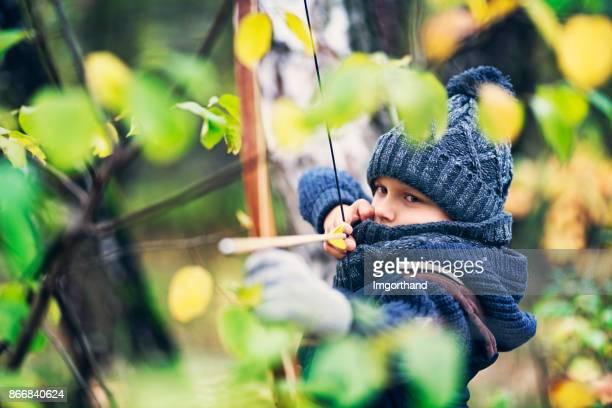 Petit garçon caché dans les buissons de la forêt et le tir arc