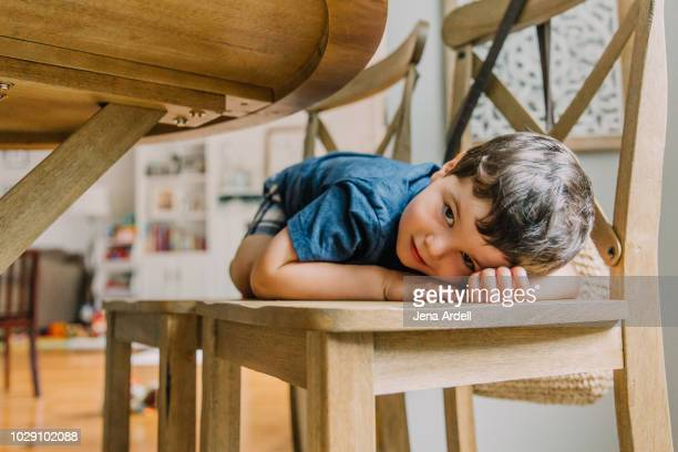 little boy hiding under table, toddler, toddler playing, little boy, child, kids, family, kid playing, boy playing, hide and seek, shy, shyness - unterhalb stock-fotos und bilder