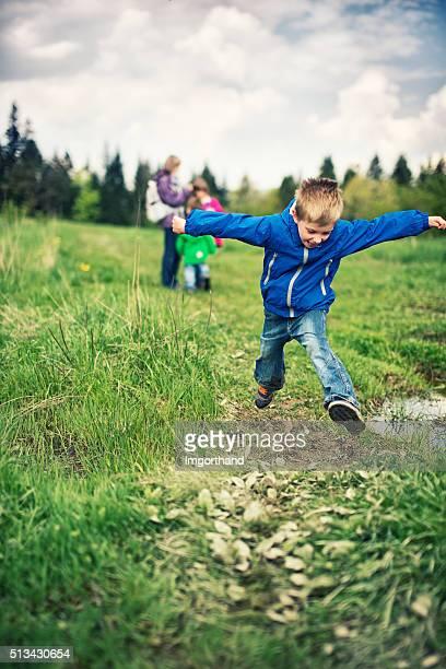 Little boy hiker jumping over mud