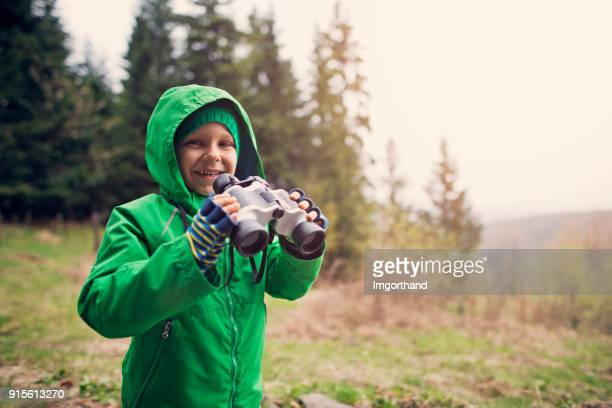 Little boy hiker looking at view with binoculars