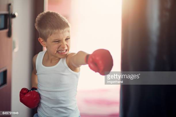 little boy hitting hard punching bag - clenching teeth stock pictures, royalty-free photos & images