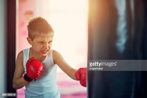 little boy hitting hard punching bag - funny boxing stock photos and pictures