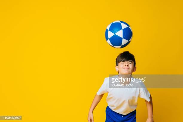 little boy hitting the ball with his head on yellow background - marcar términos deportivos fotografías e imágenes de stock