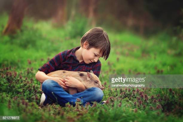 little boy holding a baby pig in his lap, looking down lovingly