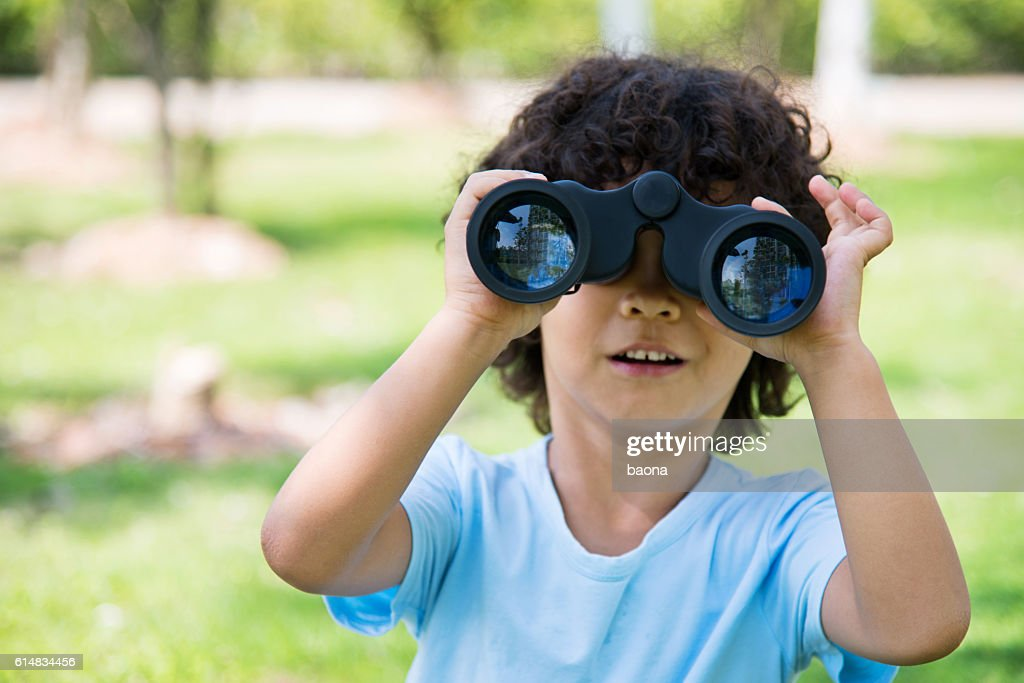 Little boy holding a binocular at park : Stock-Foto