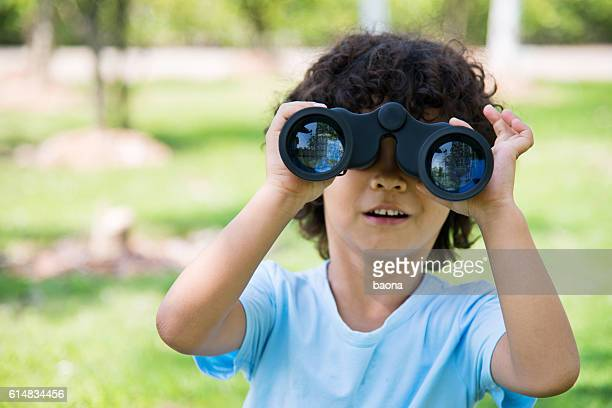 Little boy holding a binocular at park