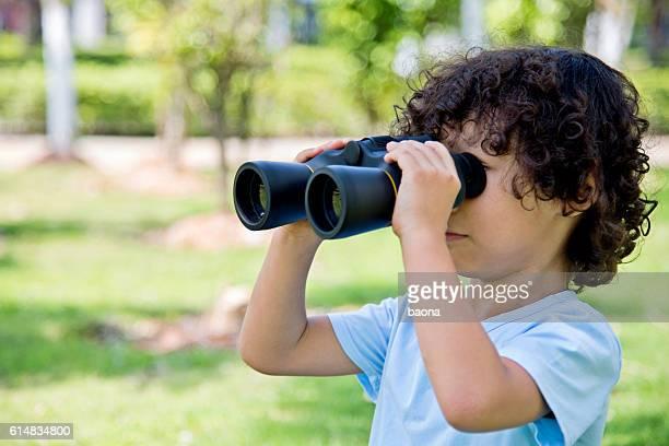 Little boy holding a binocular at park