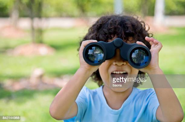 little boy holding a binocular at park - surveillance stock photos and pictures