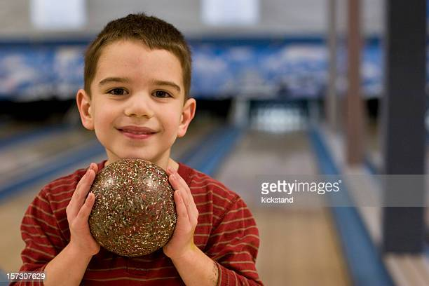 A little boy holding a bowling ball in a bowling alley